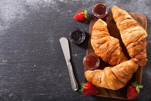 Café da manhã com croissants, geléia e morangos na mesa escura, vista de cima