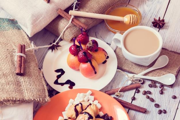 Café da manhã com croissants, mel e canapés de morangos e damascos