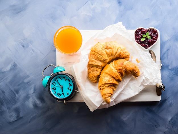Café da manhã com croissants servidos na tábua de madeira
