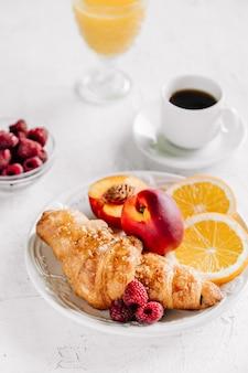 Café da manhã com croissants, uma xícara de café, framboesas e suco de laranja vista superior