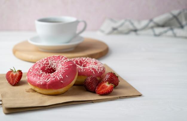 Café da manhã com deliciosos donuts com cobertura de morango e café preto na mesa branca