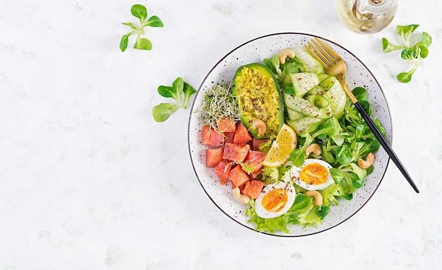 Café da manhã com dieta cetogênica. salada de salmão com verduras, pepinos, ovos e abacate. almoço keto / paleo. vista superior, sobrecarga