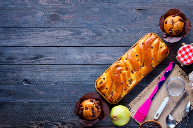 Café da manhã com diferentes bolos e frutas em uma mesa de madeira