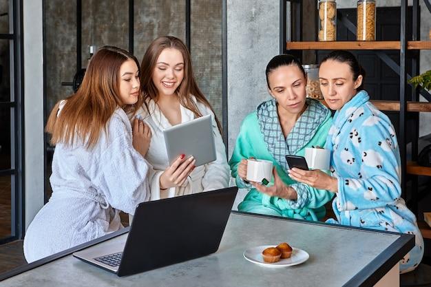 Café da manhã com dispositivos móveis, as mulheres leem mensagens e notícias online à mesa de jantar pela manhã.