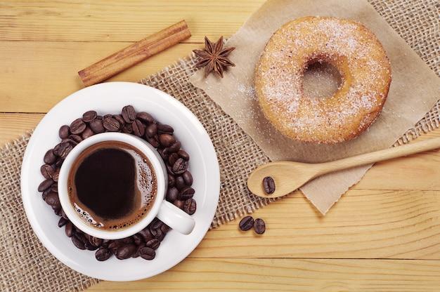 Café da manhã com donut doce e xícara de café quente na mesa de madeira