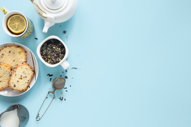 Café da manhã com ervas e coador de chá no pano de fundo colorido