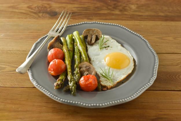 Café da manhã com espargos, ovo frito e tomate cereja. mesa de madeira.