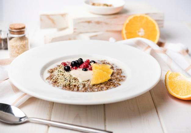 Café da manhã com fatias de laranja e sementes vista frontal