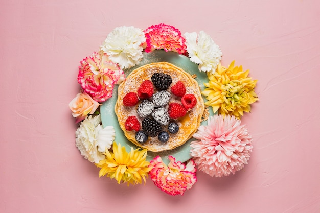 Café da manhã com flores e fundo rosa