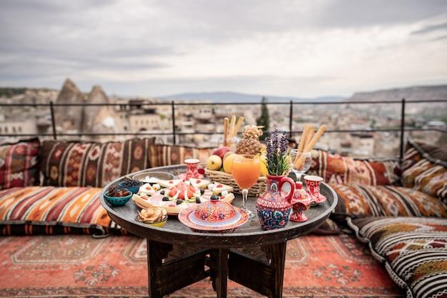 Café da manhã com grande paisagem no telhado da casa da caverna na cidade de goreme, na capadócia turquia.
