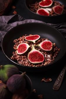 Café da manhã com granola e figos. pratos pretos com um pequeno-almoço fresco e saudável. comida saudável