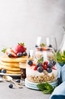 Café da manhã com granola, panquecas e frutas