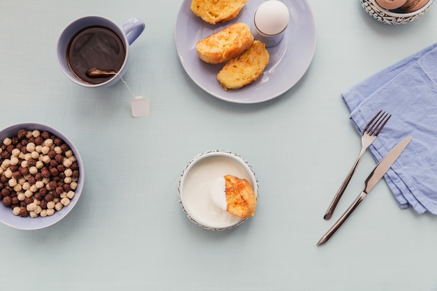 Café da manhã com iogurte croutons fritos e chá preto em comida country de verão com superfície de madeira leve