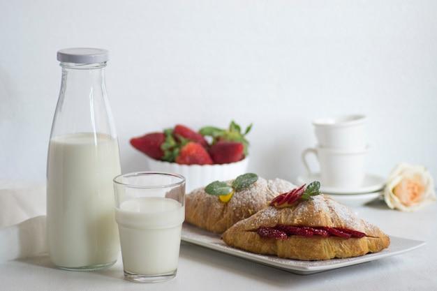 Café da manhã com leite fresco, croissant e morangos na superfície branca