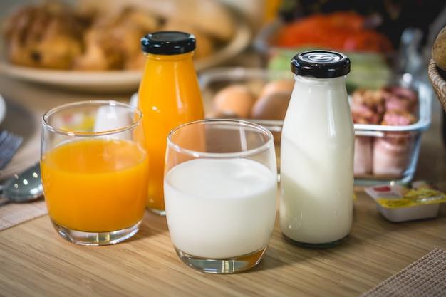 Café da manhã com leite, suco de laranja, pão francês ou baguete com a mesa de jantar de manhã