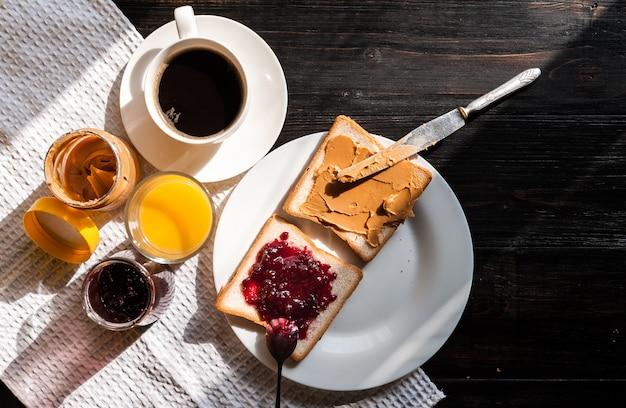 Café da manhã com manteiga de amendoim e geléia e uma xícara de café em uma mesa de madeira ao sol da manhã