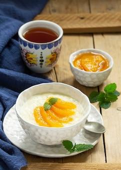 Café da manhã com mingau de arroz com geléia de pêssego e chá. estilo rústico.