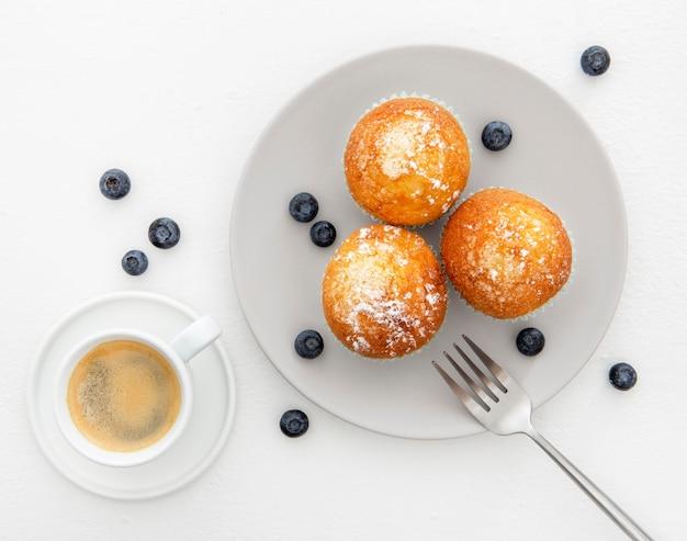 Café da manhã com muffins e café plano