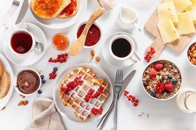 Café da manhã com nozes de granola, waffle, torradas, geléia, chocolate e café. vista do topo