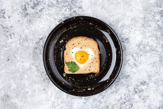 Café da manhã com ovo cozido em forma de coração em uma fatia de torrada