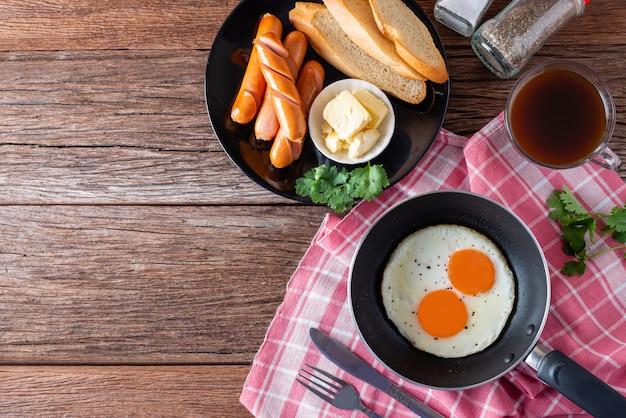 Café da manhã com ovo frito na panela e salsicha grill com torradas, café na mesa