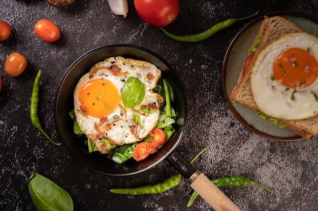 Café da manhã com ovos fritos, salsicha e presunto em uma panela com tomate. pimenta e manjericão