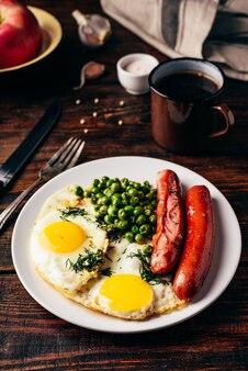 Café da manhã com ovos fritos, salsichas e ervilhas em prato branco