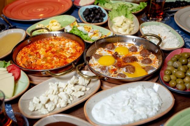 Café da manhã com ovos mexidos, azeitonas, queijo branco e creme de leite