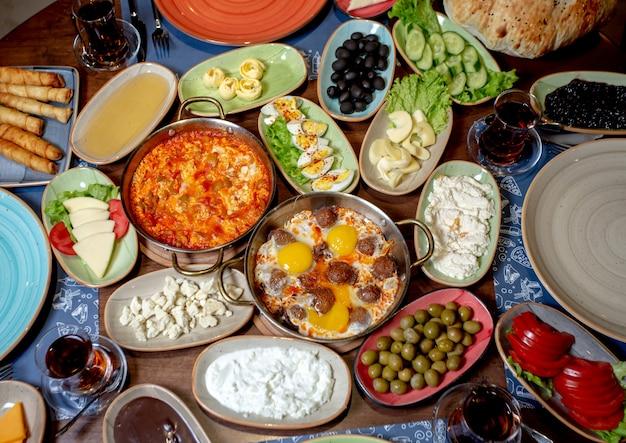 Café da manhã com ovos mexidos, azeitonas, queijo branco, pepino, tomate e chá