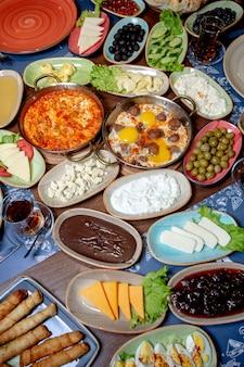 Café da manhã com ovos mexidos, azeitonas, queijo, chá, creme de chocolate e geléia