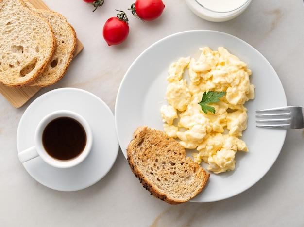 Café da manhã com ovos mexidos fritos, xícara de café, tomates no fundo de pedra branco