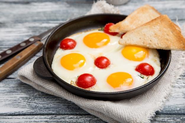 Café da manhã com ovos, tomate cereja, bacon e torradas frescas torradas