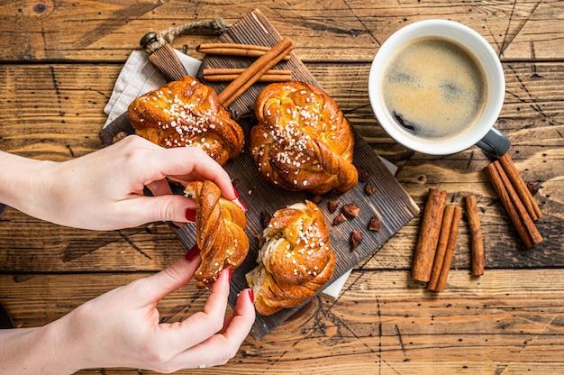 Café da manhã com pãezinhos de canela ou pãezinhos, kanelbullar sueco. fundo de madeira. vista do topo.