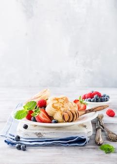 Café da manhã com panquecas escocêsas em forma de flor, bagas e mel na mesa de madeira clara.