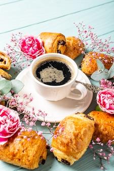 Café da manhã com pão de mini croissants frescos com xícara de chocolate e café na superfície azul turquesa. copie o espaço