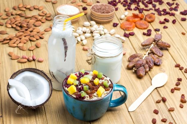 Café da manhã com proteína balanceada de muesli. frutas, sementes de bagas, nozes, coco. bebida de coco e iogurte. comida vegetariana de dieta saudável. vista superior fundo de madeira. copie o espaço