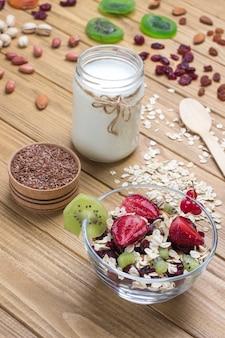 Café da manhã com proteína balanceada de muesli. frutas, sementes de bagas, nozes. iogurte de coco. comida vegetariana de dieta saudável. vista superior superfície de madeira. copie o espaço