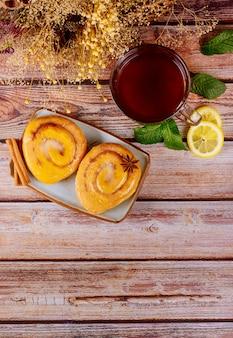 Café da manhã com rolos de canela vitrificada e xícara de chá com limão e hortelã