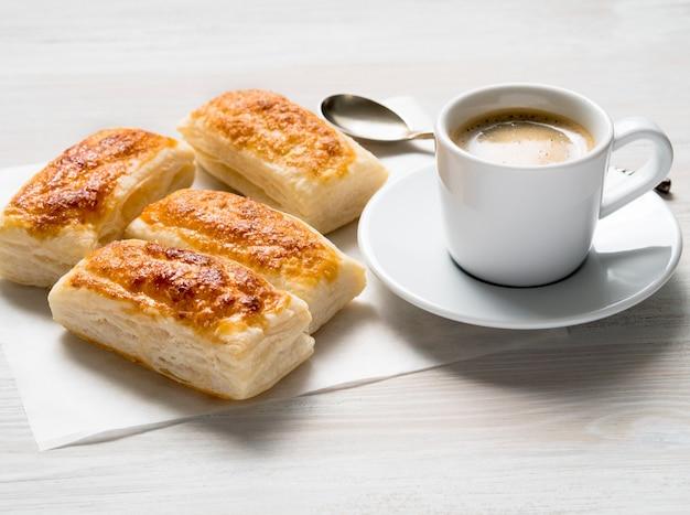 Café da manhã com rolos frescos de massa folhada e xícara de café na mesa de madeira branca.