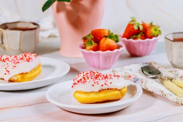 Café da manhã com rosquinha doce polvilhe, morango e xícara de café.