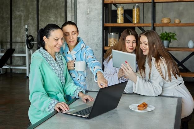 Café da manhã com roupões de banho, família de quatro mulheres conversando durante o chá e vendo informações em dispositivos móveis à mesa da sala de jantar.