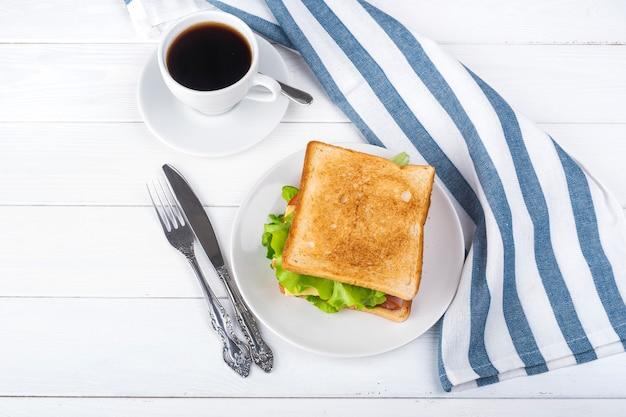 Café da manhã com sanduíche e café.