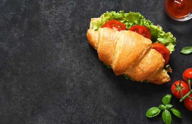 Café da manhã com sanduíches de croissant com folhas de salada, presunto e tomate cereja, com molho em um fundo preto. vista de cima.