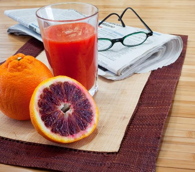 Café da manhã com suco de laranja e jornal