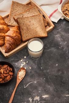 Café da manhã com torradas e croissant. leite em uma garrafa de vidro. bom começo de dia. bom dia