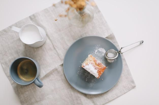 Café da manhã com um pedaço de jarra de bolo caseiro fresco e uma xícara de café na mesa