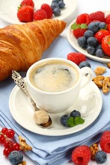 Café da manhã com uma xícara de café, croissants e frutas