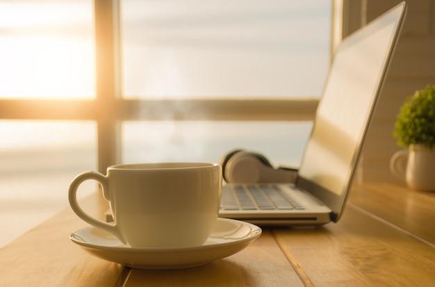 Café da manhã com uma xícara de café quente em cima da mesa no escritório que possui um laptop.