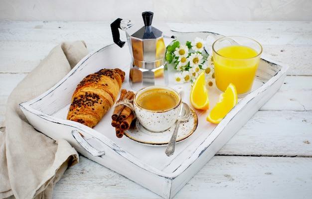 Café da manhã com uma xícara de croissants de café e suco de laranja