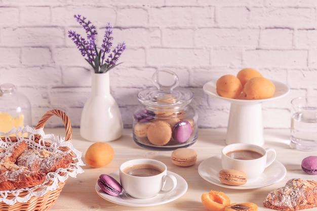 Café da manhã com vários biscoitos, croissants e chocolate quente.